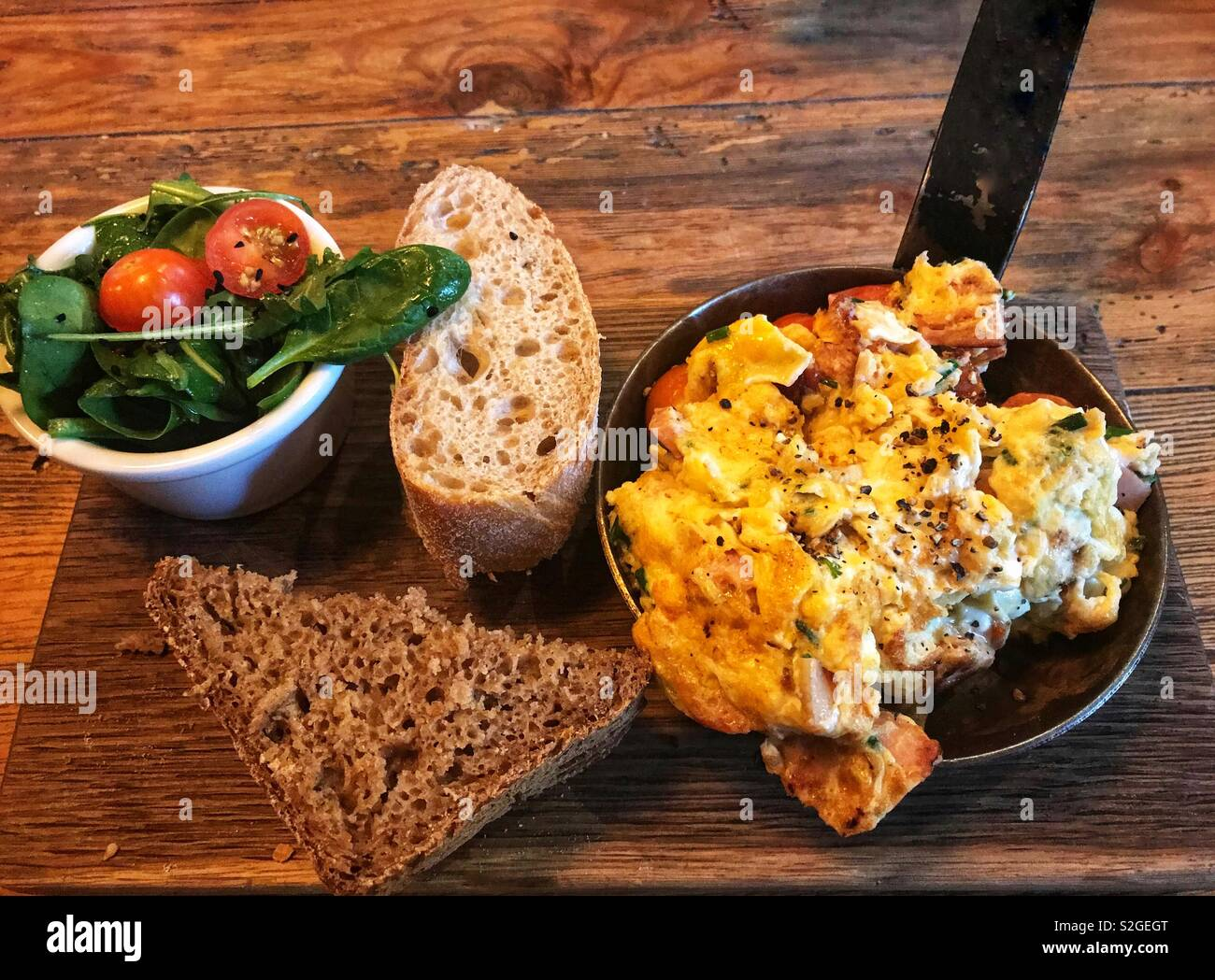 Scrambled eggs served in individual cast iron pan, salad and bread for breakfast - Stock Image