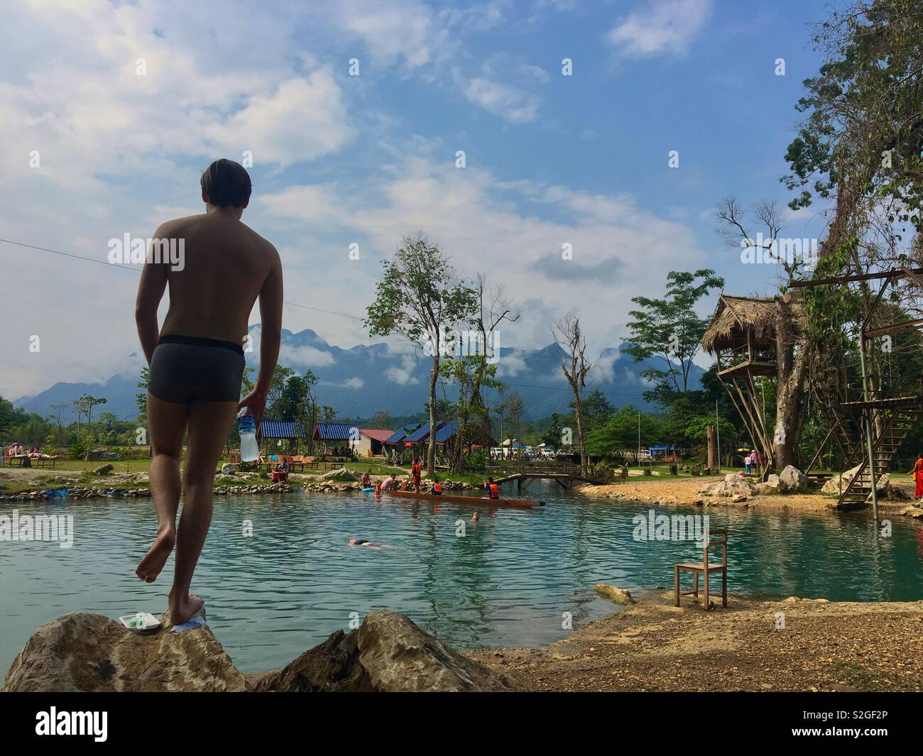 Tourist at watering hole in Laos - Stock Image