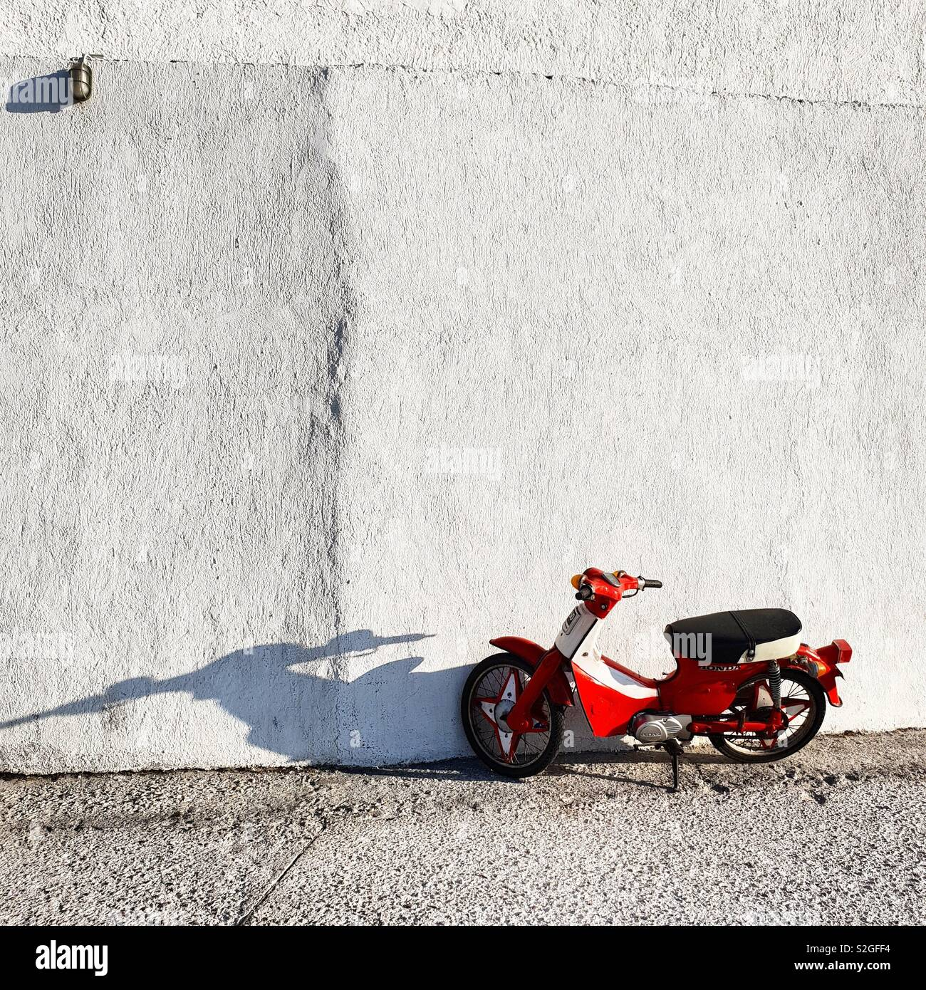 Red scooter and white wall in Milos Island, Greece - Stock Image