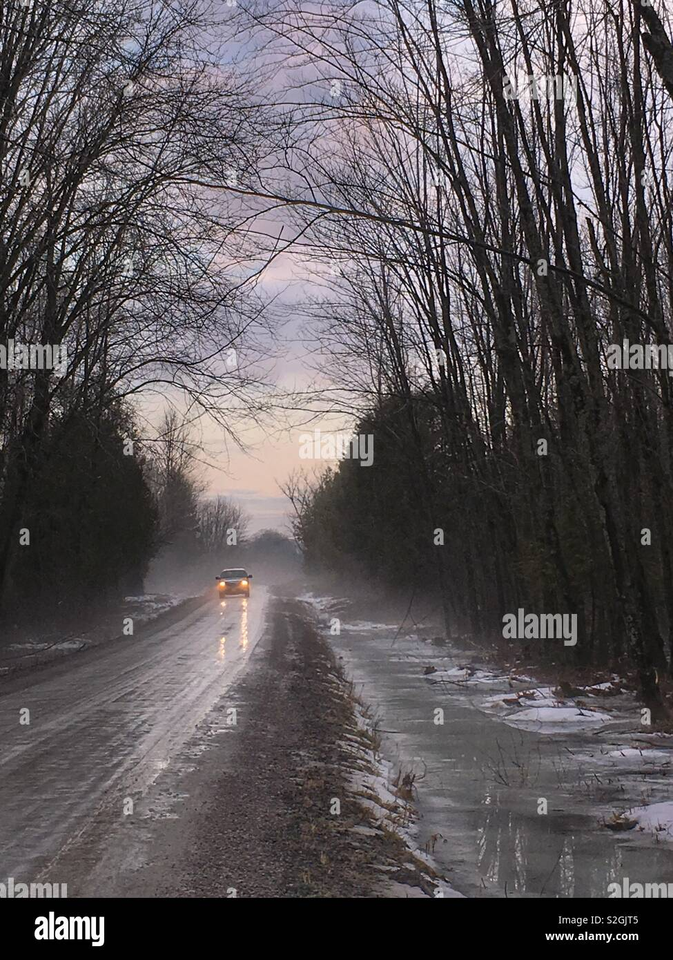 Moody uneasy shot, pick up truck with lights on, coming thru the cold winter mist down a long water covered rural road, with the roadside ditch iced over. - Stock Image