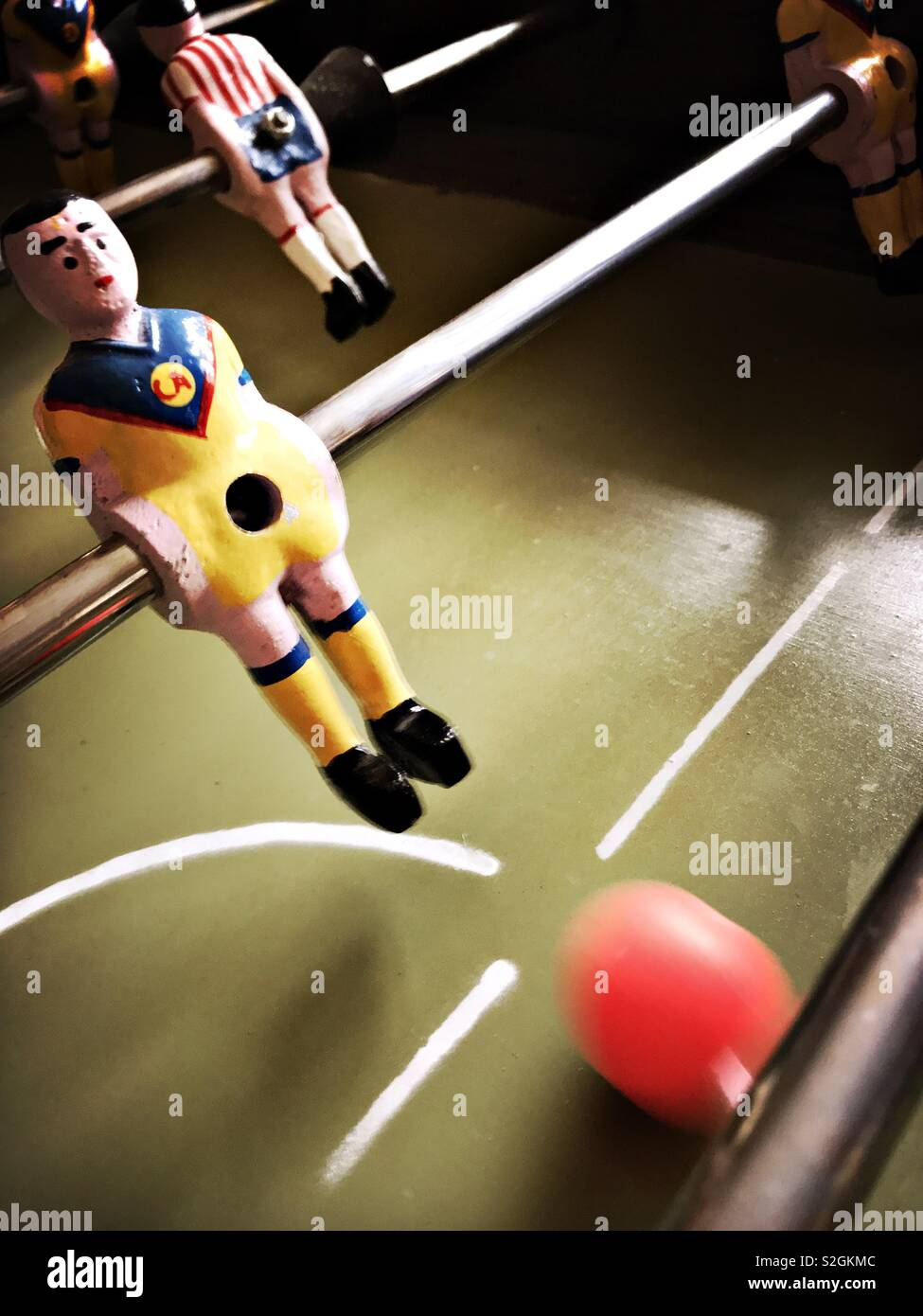 A Club America futbolito figure kicks the ball down the tabletop field during a fast paced game against the rival Chivas team. - Stock Image