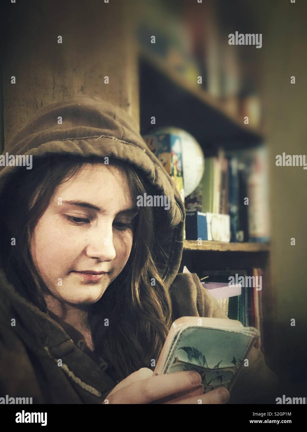 Candid portrait of teenage girl reading on her smartphone - Stock Image