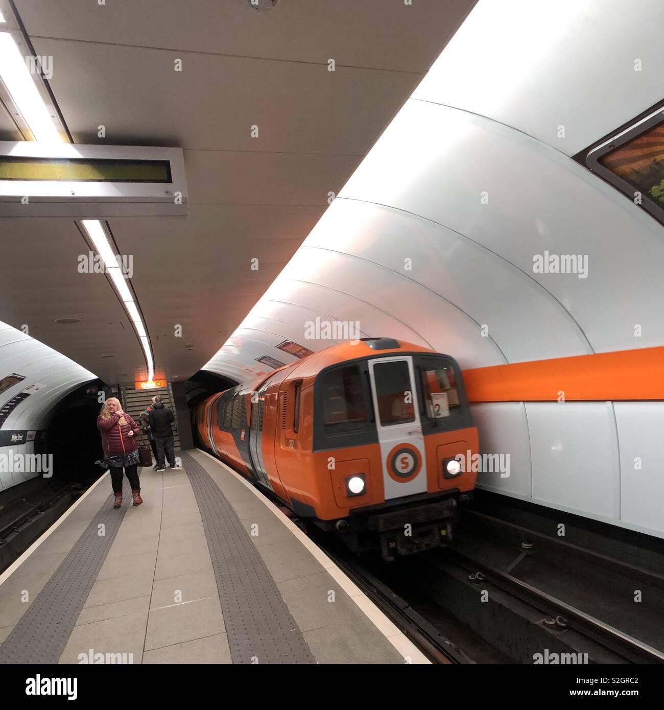 Glasgow subway train arriving at station. Scotland. UK. - Stock Image