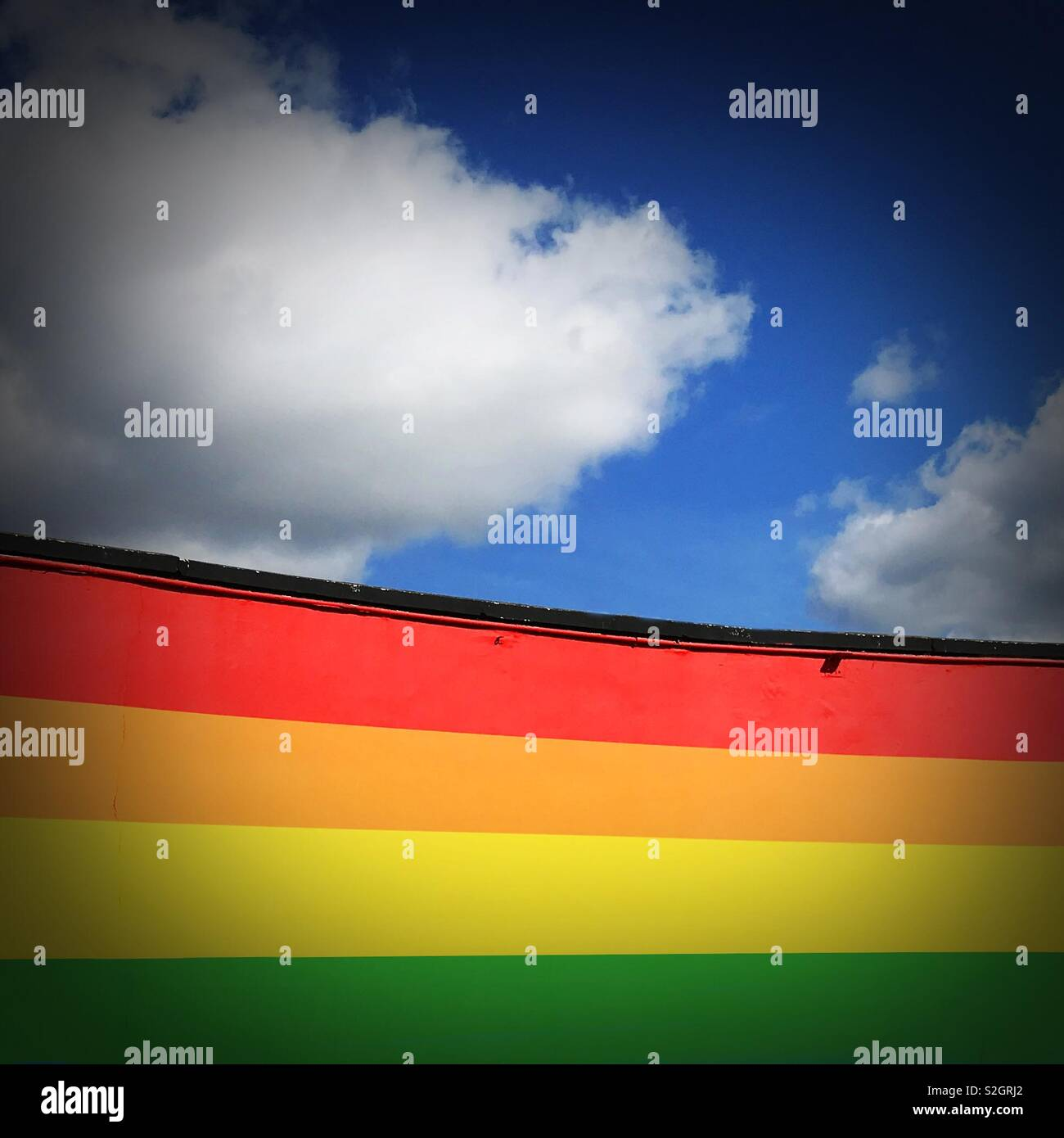 Wall painted in rainbow colors against a blue sky with white clouds - Stock Image
