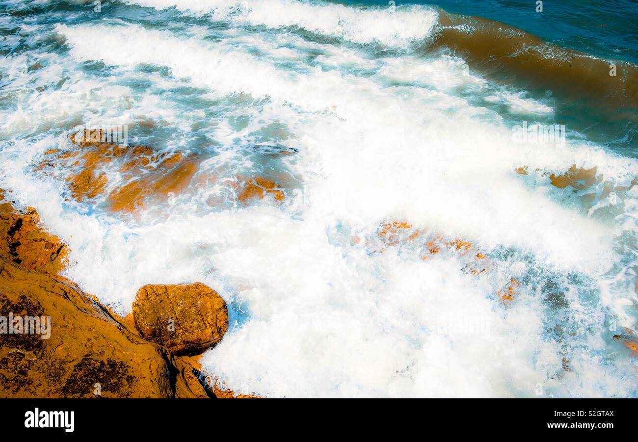 Ocean waves crashing against the rocks below, blue green water, white dreamy waves. Stock Photo