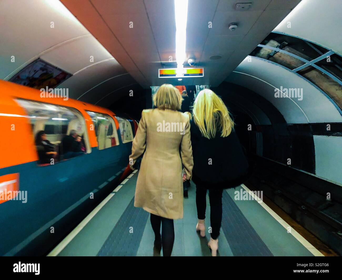 Train leaving station and passengers leaving platform, Glasgow subway. Scotland. UK. - Stock Image