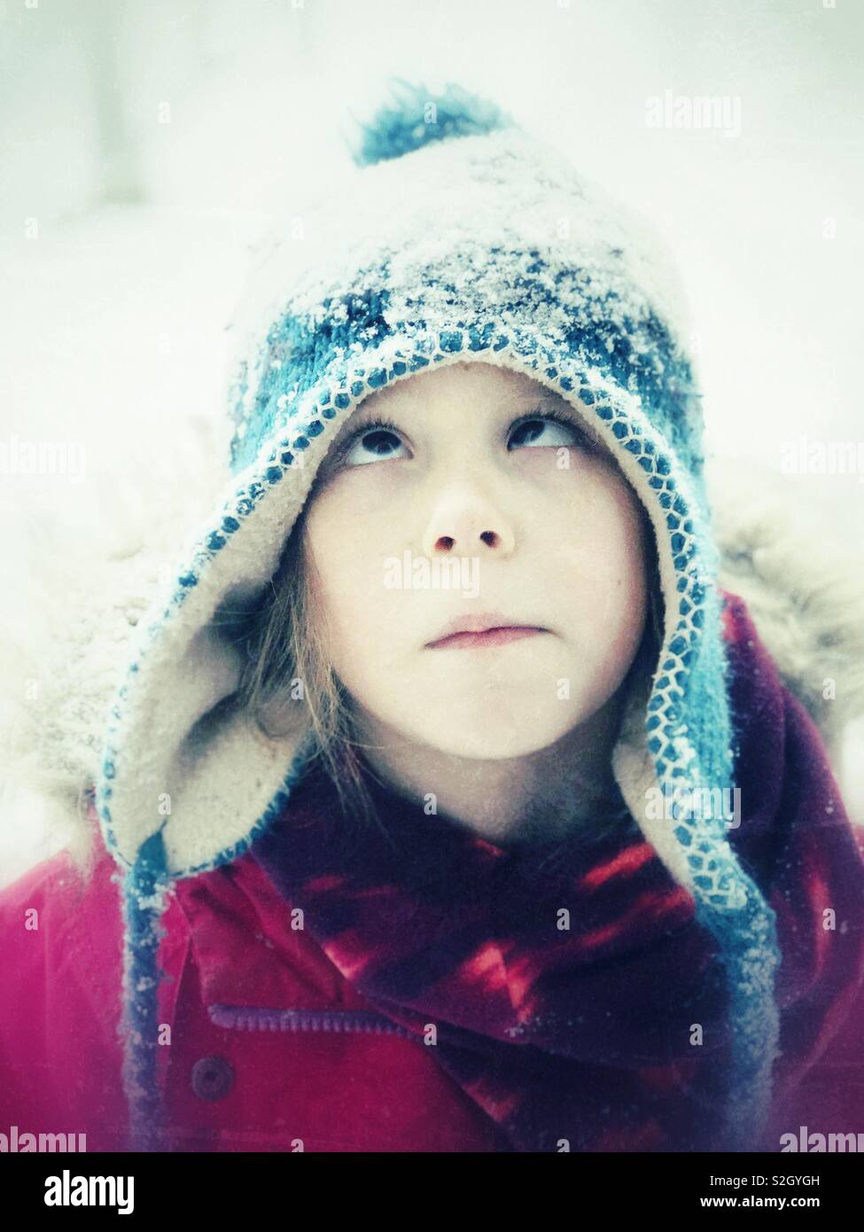 Silly portrait of 6 year old girl crossing eyes looking up at snow on her head - Stock Image