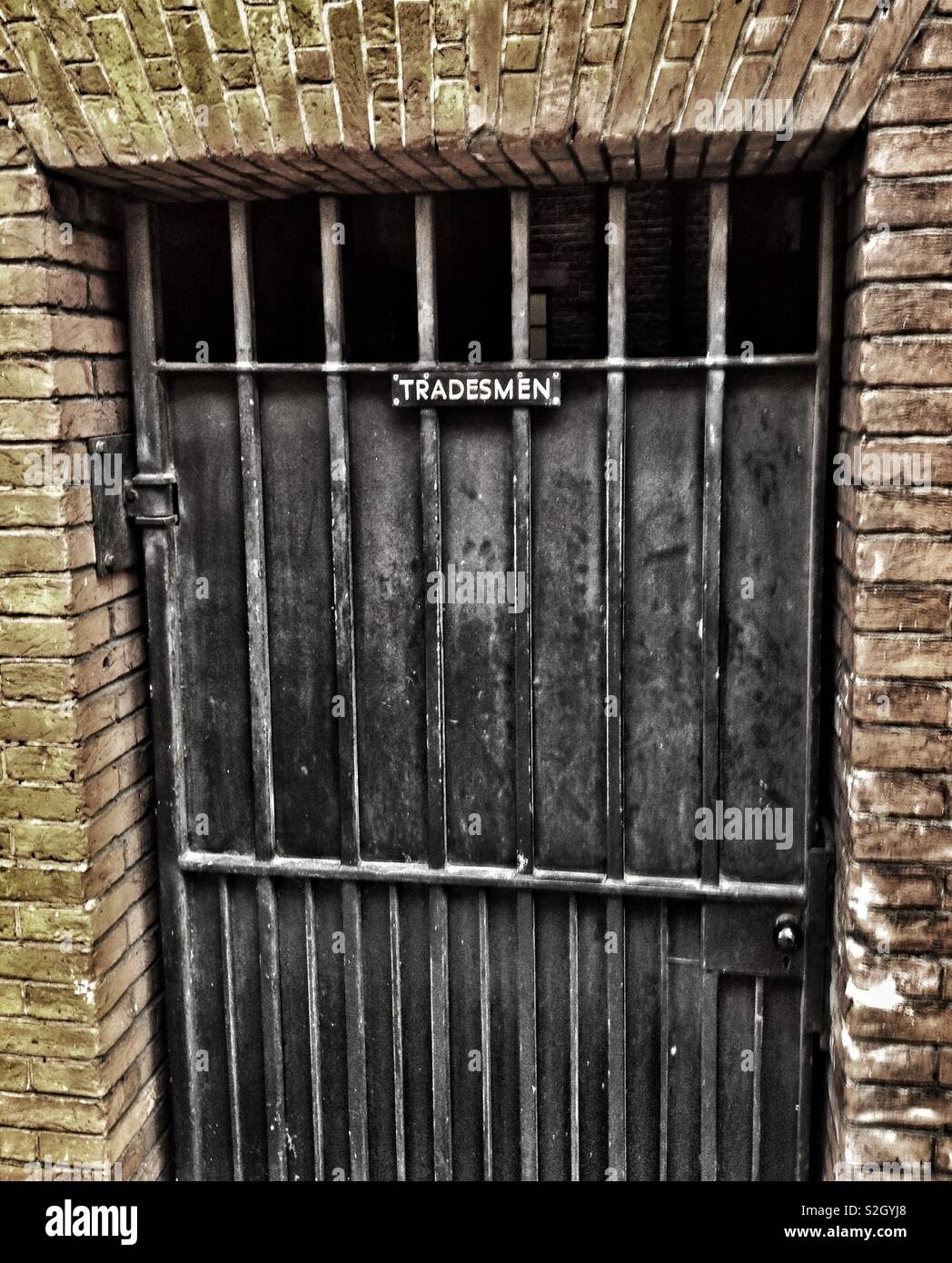 An old fashioned tradesmen entrance sign on the gate of a house in central London, England - Stock Image