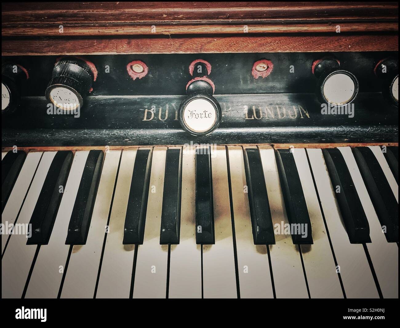 Stop faces on antique pump organ at Toeka Stoor, South Africa. - Stock Image