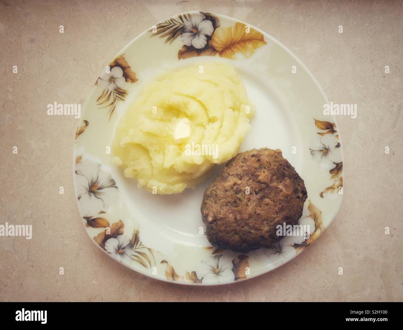 Top view on a triangle shape plate with potato mash and homemade cutlet - Stock Image