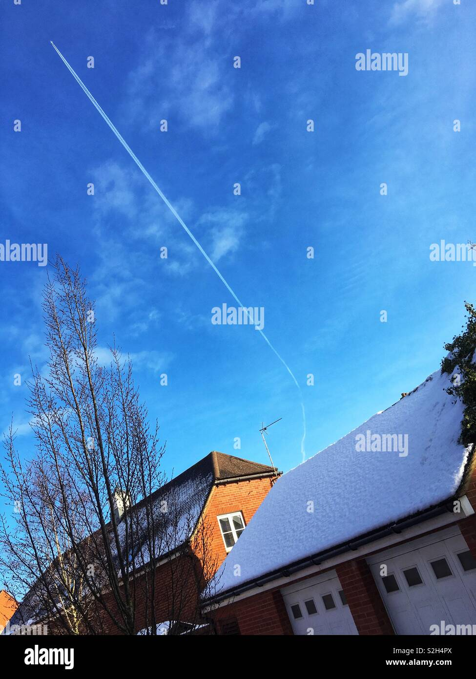 Angled shot of roofs with snow, featuring a high plane with diagonal vapour train in a blue sky. Copy space. - Stock Image