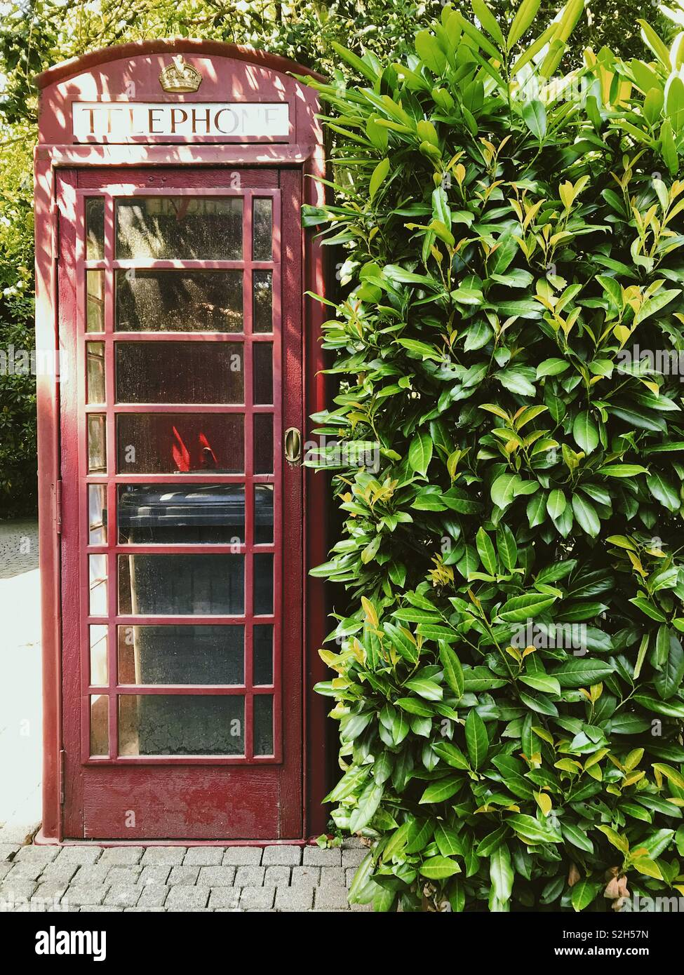 British telephone cabin with a trash can inside - Stock Image
