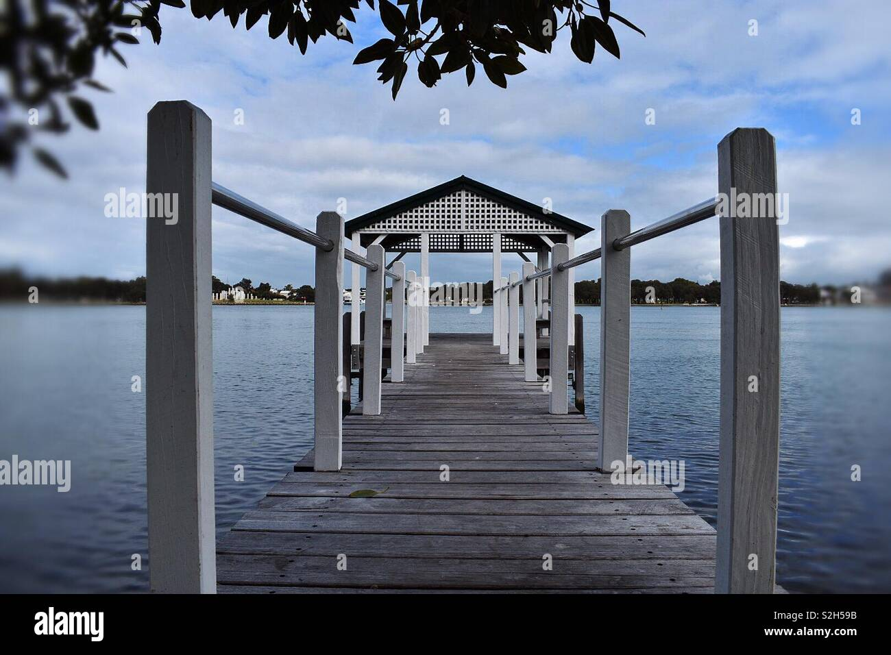 Mid shot of an old jetty located on the boarder of the Mandurah Estuary, Western Australia. - Stock Image