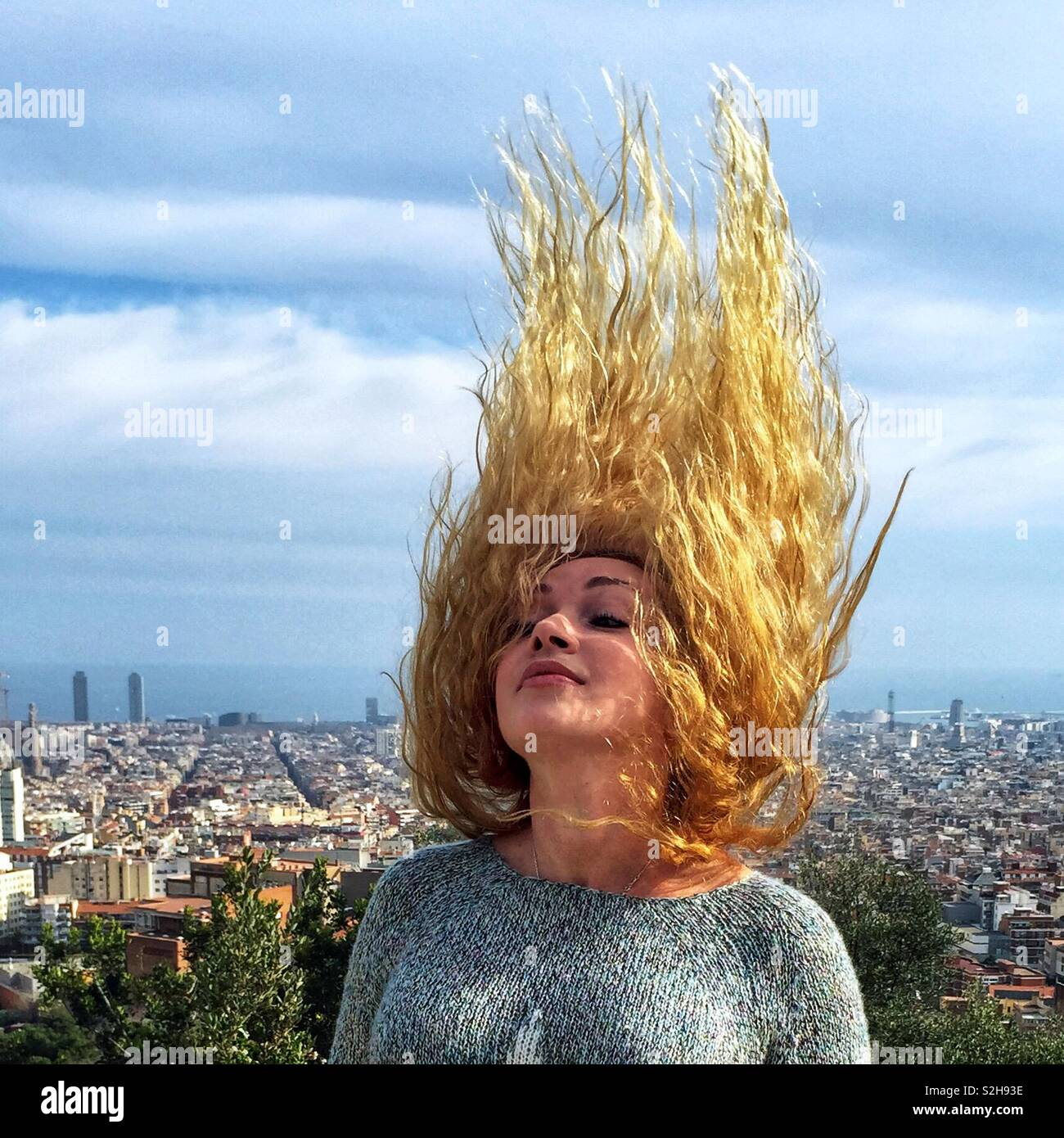 Portrait of a blonde girl with long curly hair that the wind is waving. She stands on a hill, below the city and the sea is visible. - Stock Image