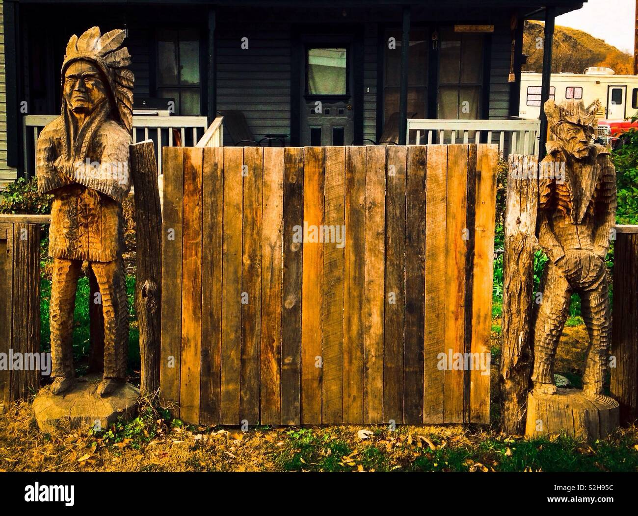 Carved wooden statue of sullen Indian chief with crossed arms and surly cowboy with hands in pockets stand on each side of wooden gate in front of house - Stock Image