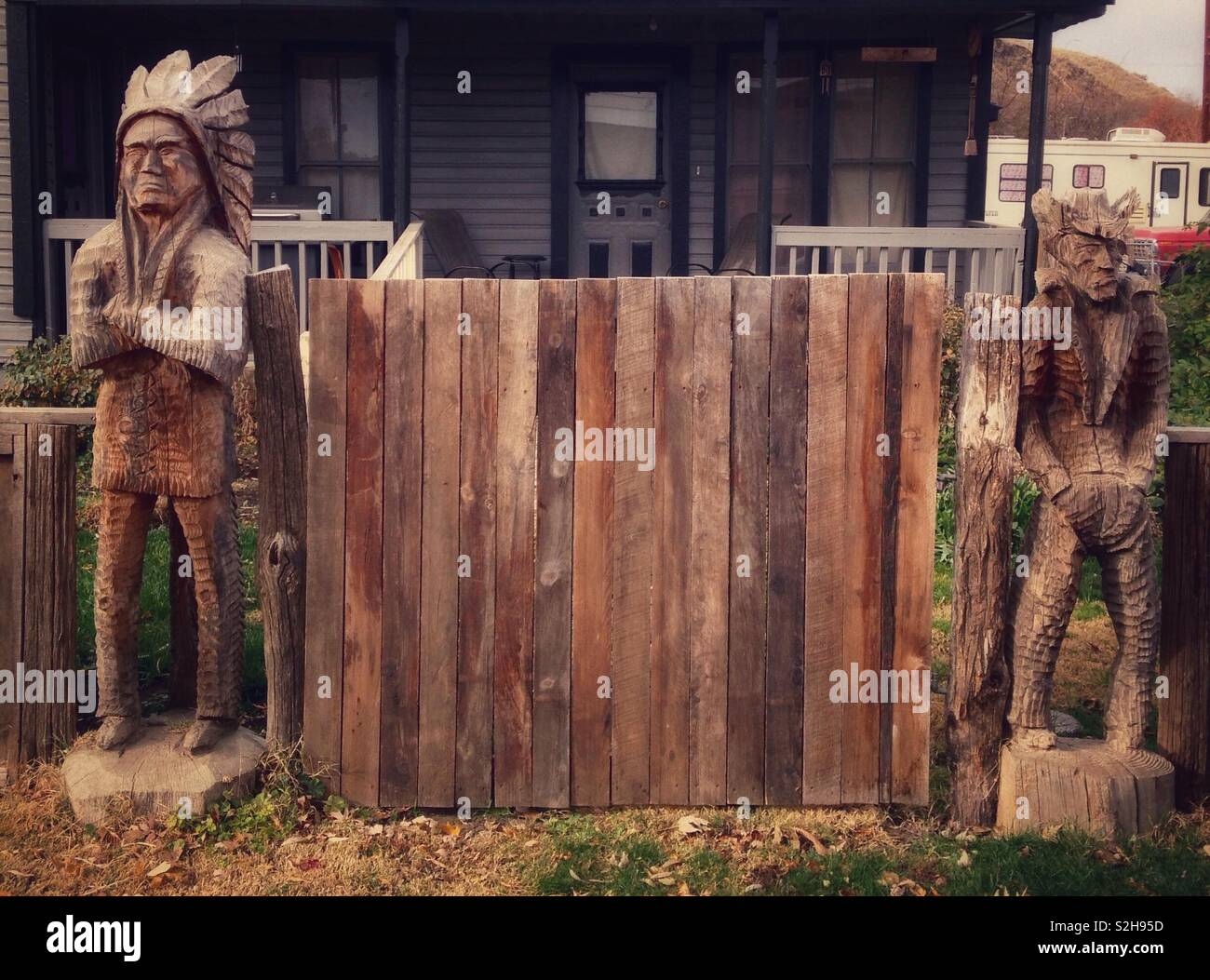 Sullen wooden Indian chief with arms crossed and surly wooden cowboy with hands in pockets stand on either side of wooden gate in front of house - Stock Image