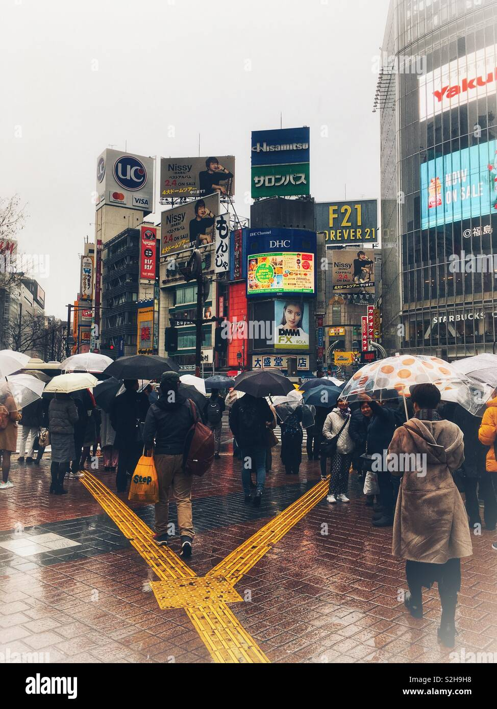 Famous Shibuya Scramble Crossing on a Rainy Day from Pedestrian Perspective - Stock Image