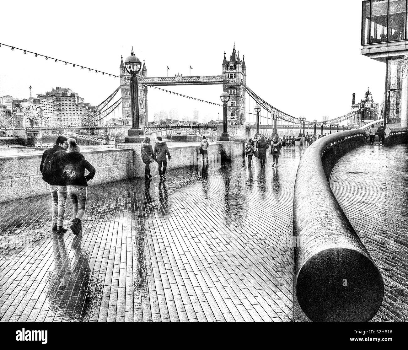 Tourists on a rainy day in London, on the Queen's Walk by the river Thames, looking towards Tower Bridge, London, England - Stock Image