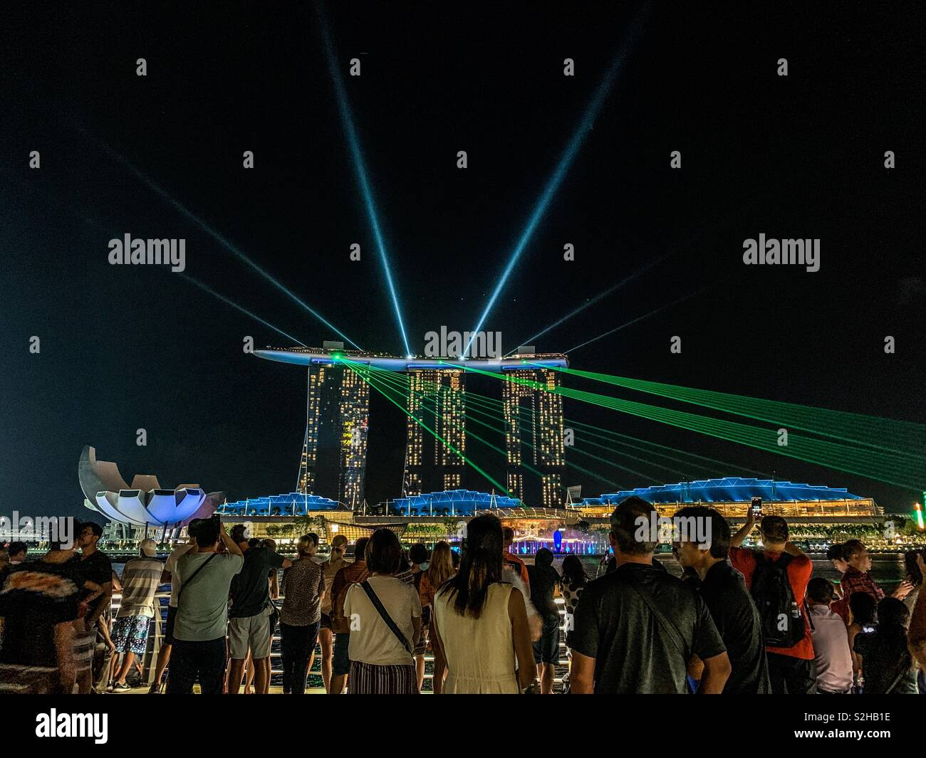 Crowd gather at the Merlion Park pavilion to watch the laser light show by Marina Bay Sands. - Stock Image