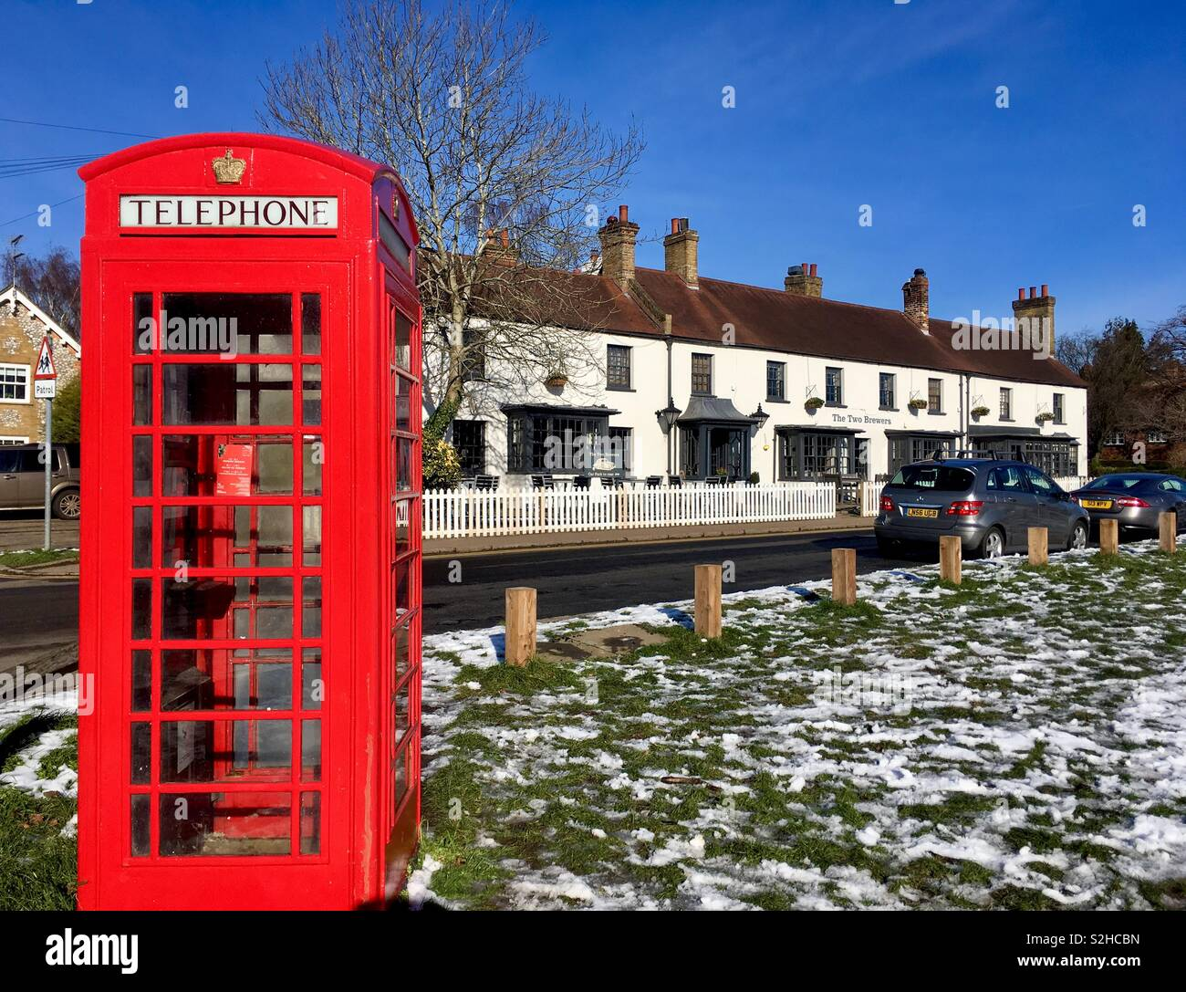 British red telephone box by village pub. - Stock Image