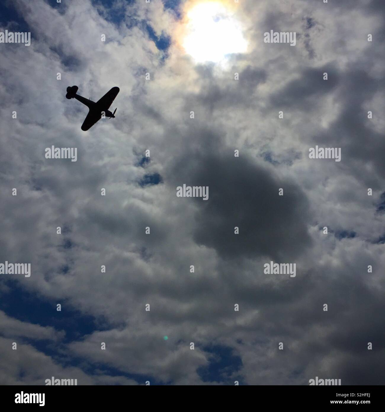 Hurricane fighter bomber silhouetted against a cloudy summer sky - Stock Image