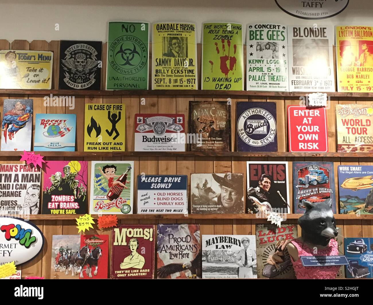 Display wall of classic vintage authentic tin foil advertisements with ad slogans.  Budweiser.  Betty Boop. Mayberry Law. - Stock Image
