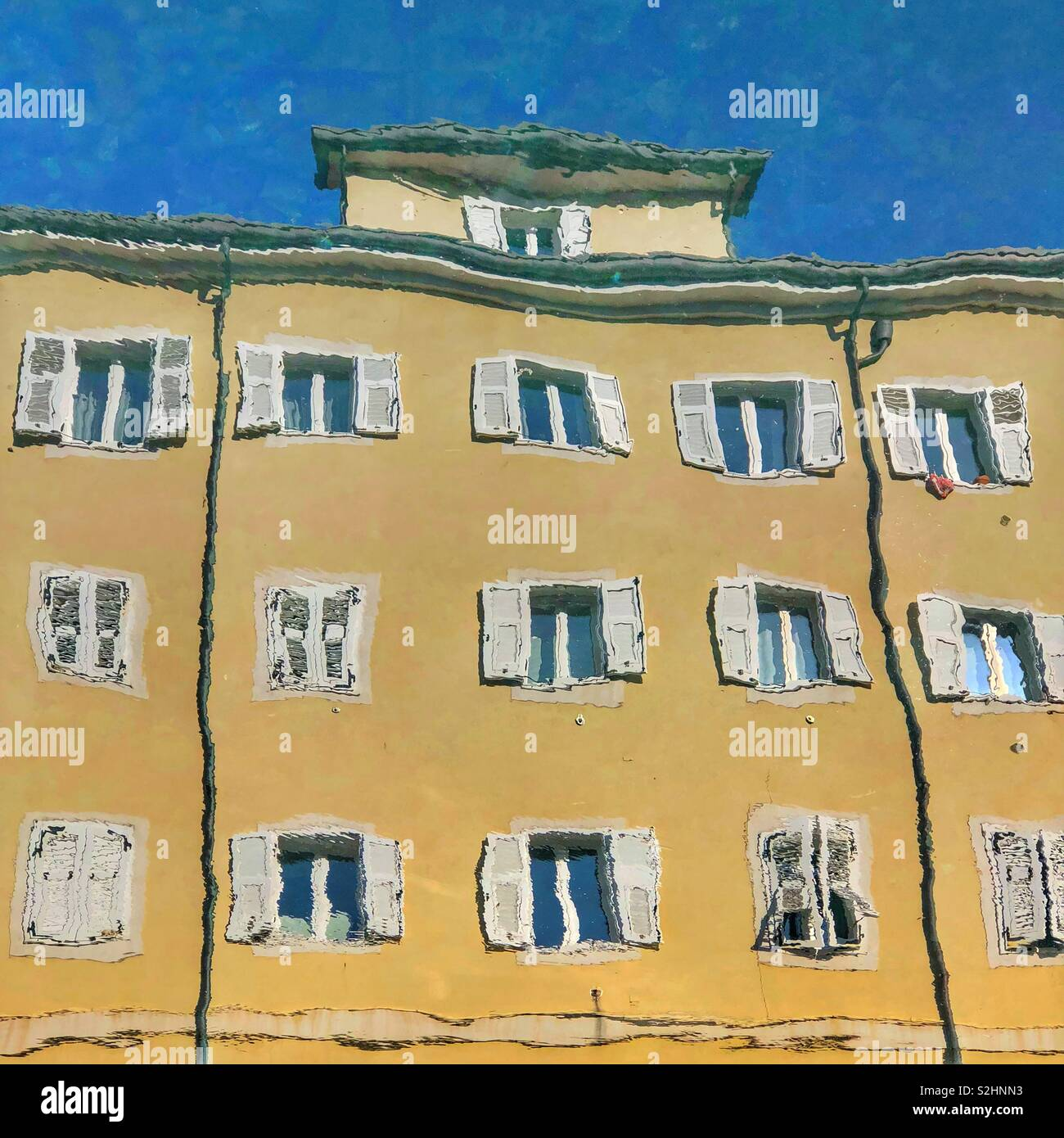 Reflections of a building in the water - Muggia, Italy - Stock Image