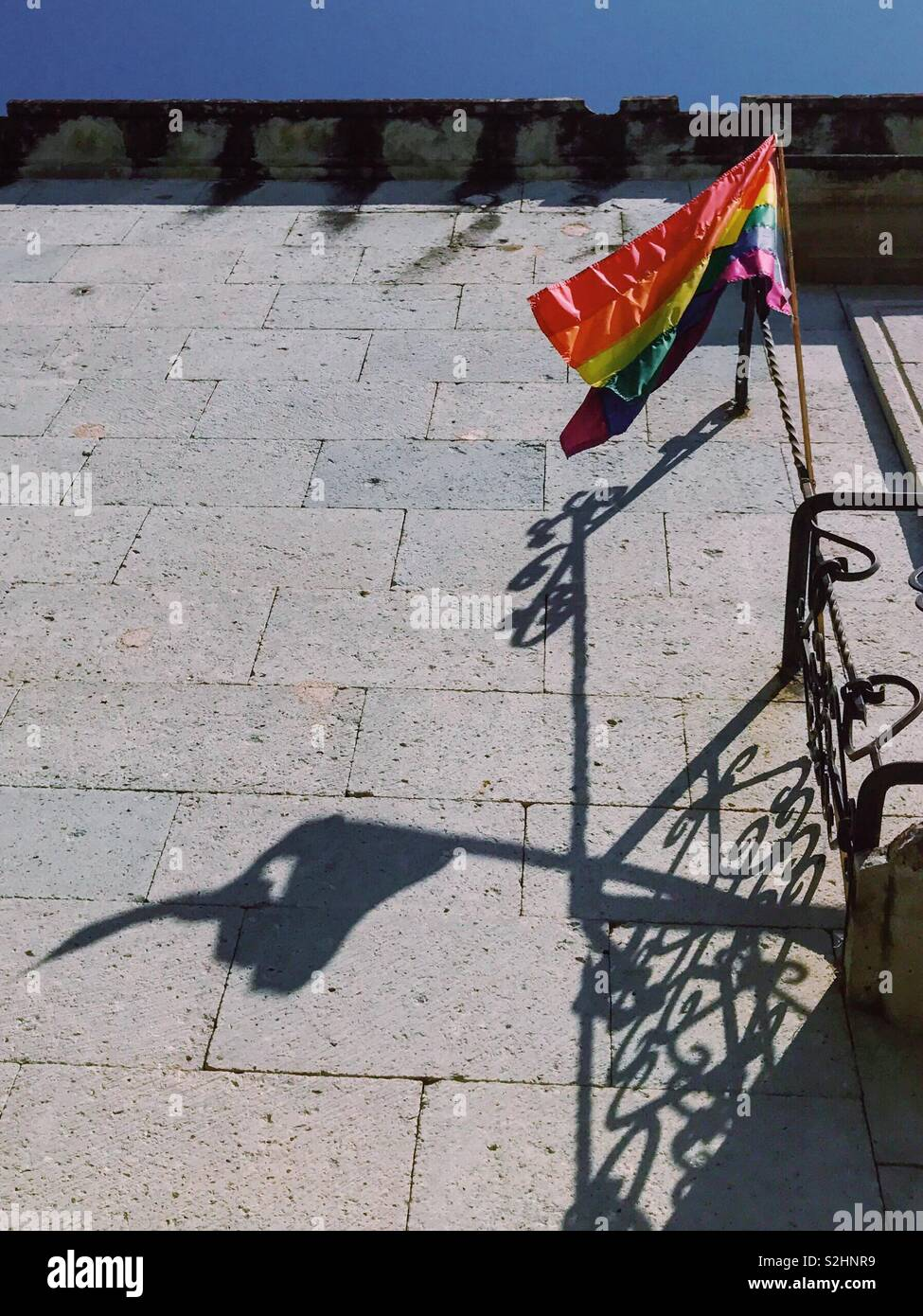 B-side of Bright Side. Bright LGBTQ flag and its torn shadow on the wall of the house. Often behind bright appearance we do not see hidden suffering and traumas. Oaxaca, Mexico. 16th of February 2019 - Stock Image