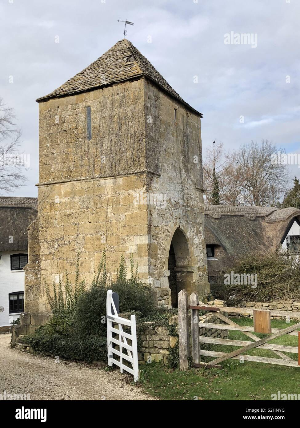 Picturesque ruin and tower all that is left of the medieval church at Gretton, near Cheltenham in the Vale of Evesham flanked by beautiful period thatched cottages. - Stock Image