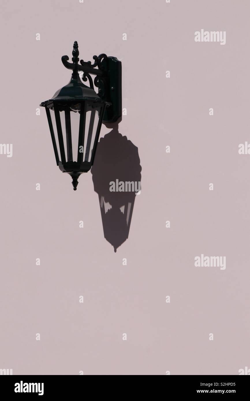 Lamp and it's shadow on a pink wall - Stock Image