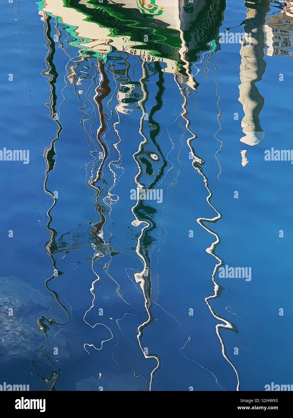 Abstract wiggly lines of white and green boat masts reflecting in bathe blue water of Santa Barbara harbor. Fall 2018 - Stock Image