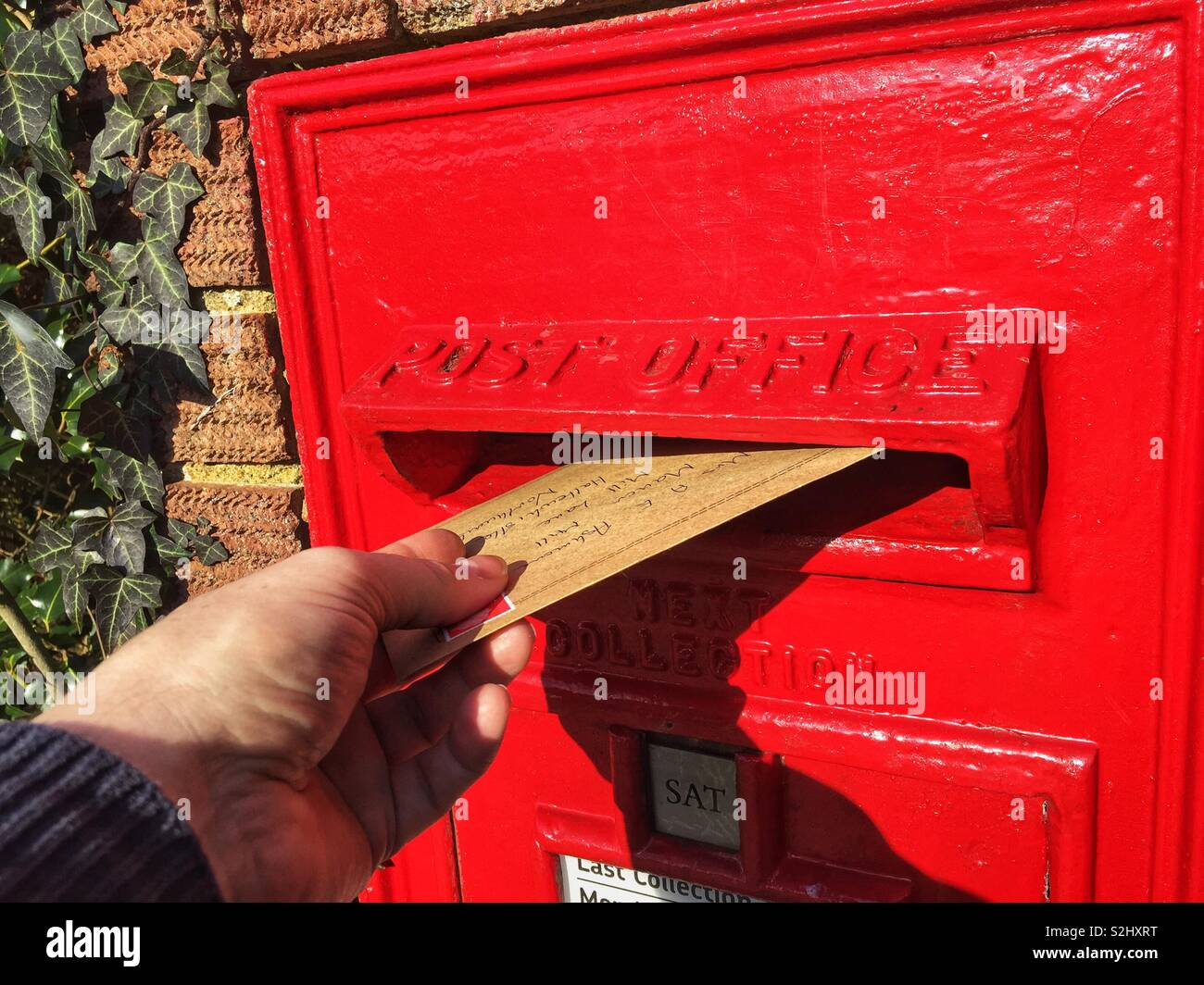 Hand posting a letter in a post box. - Stock Image