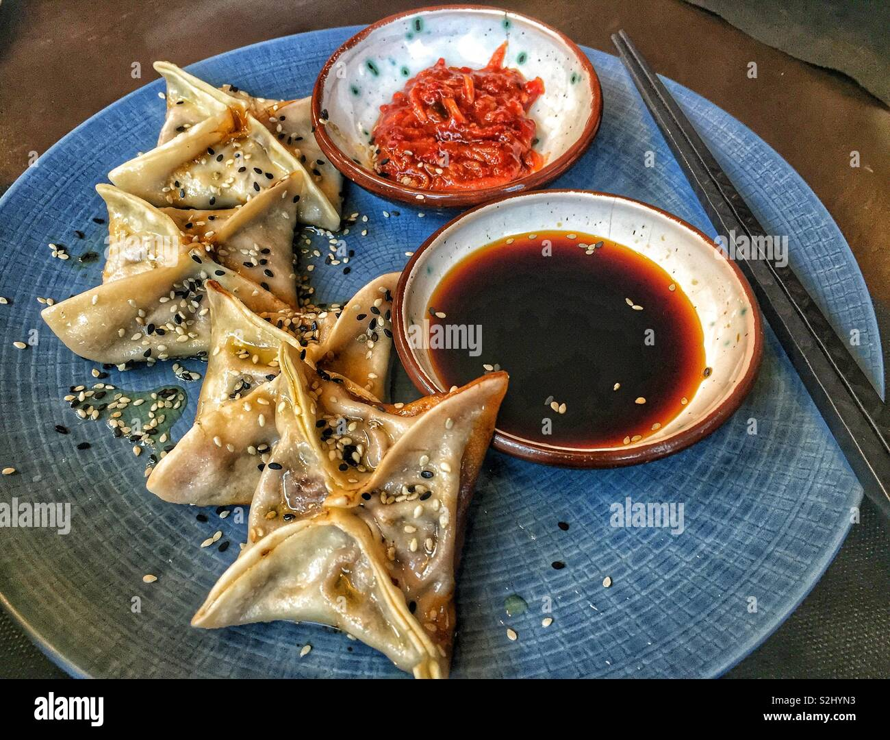 Chinese dumplings served with soya souse and chili - Stock Image