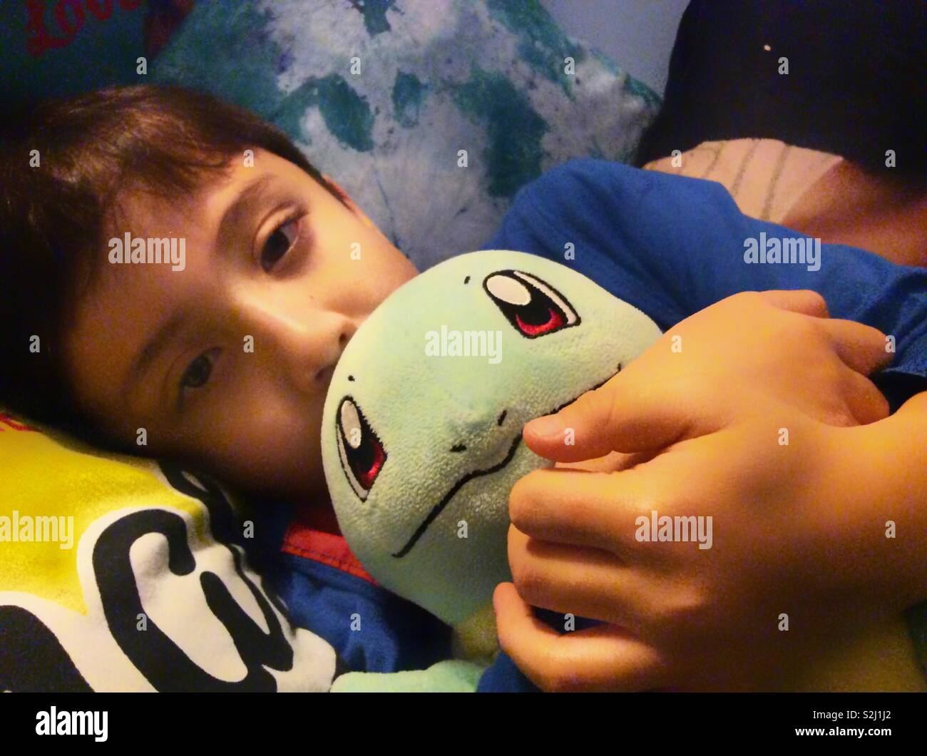 A young boy lying down in bed cuddling a cuddly toy. - Stock Image