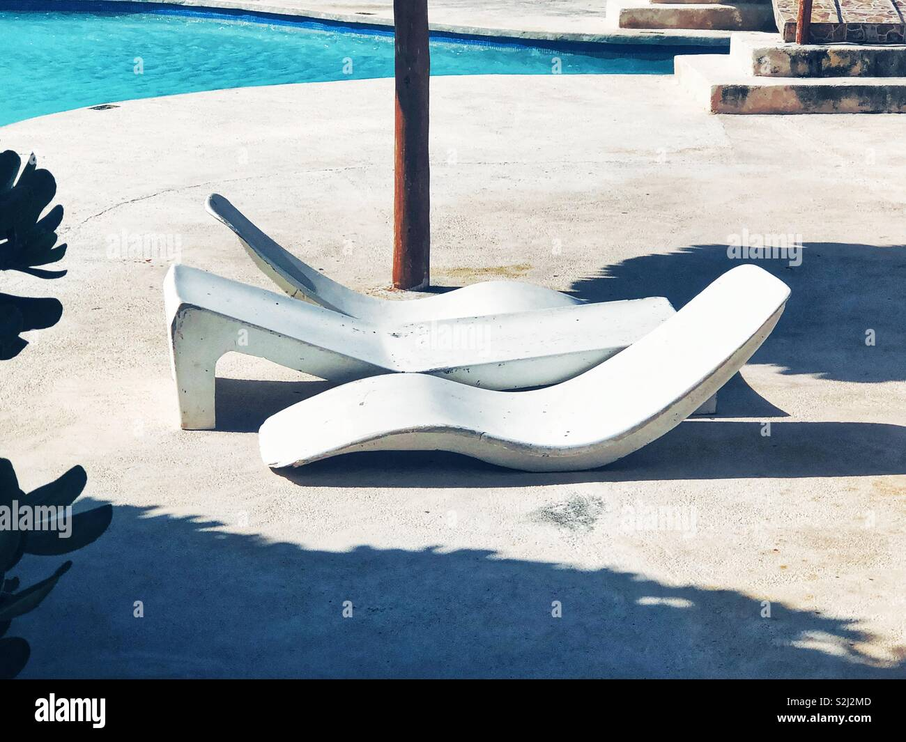 modern chaise lounges by the pool in Mexico - Stock Image
