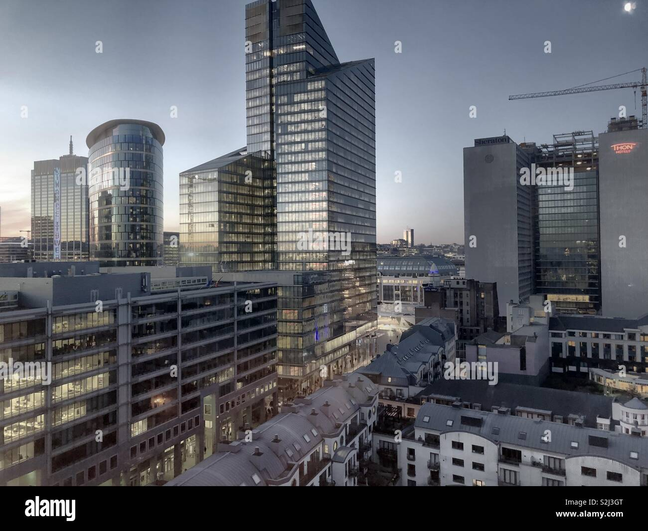 A full spectrum of colors during sunrise shown in the sky and the reflection of the sky in the glass of the business offices of the financial district of the city - Stock Image