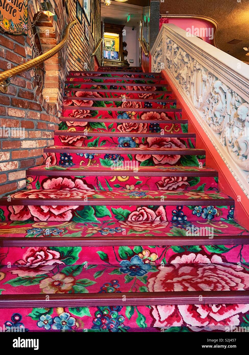 Wild pink floral carpet and staircase at the Madonna Inn in San Luis Obispo California - Stock Image