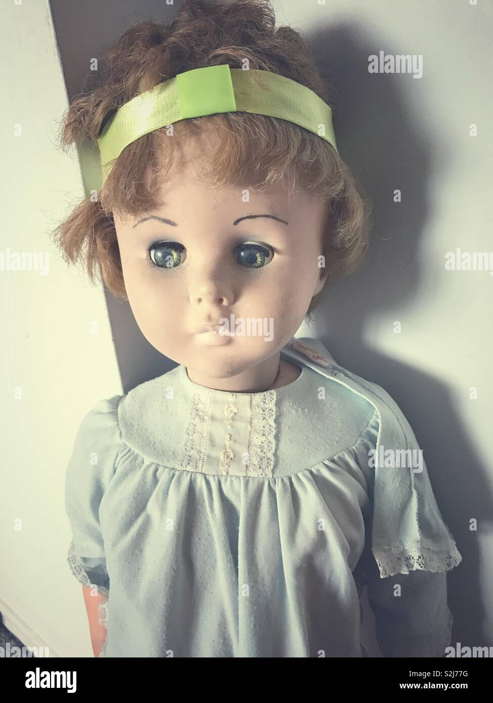 vintage children's doll from the 1960s or 1970s, worn out looking, with cut hair. - Stock Image