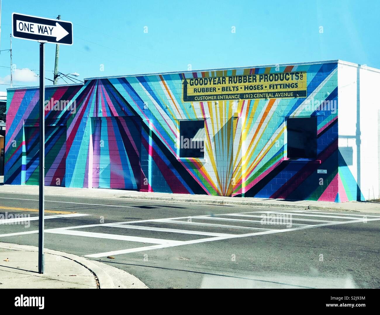Colorful stripy mural on old brick building in downtown Saint Petersburg, Florida - Stock Image