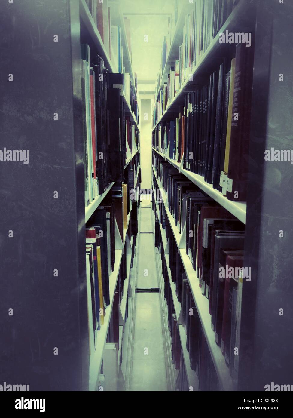 Between two moving book shelves in a library - Stock Image