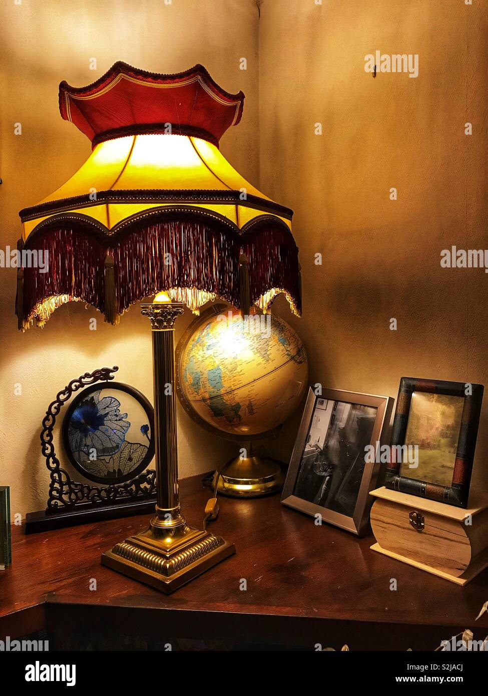 A lamp, family photos and a globe on a ledge in a corner of a room. - Stock Image