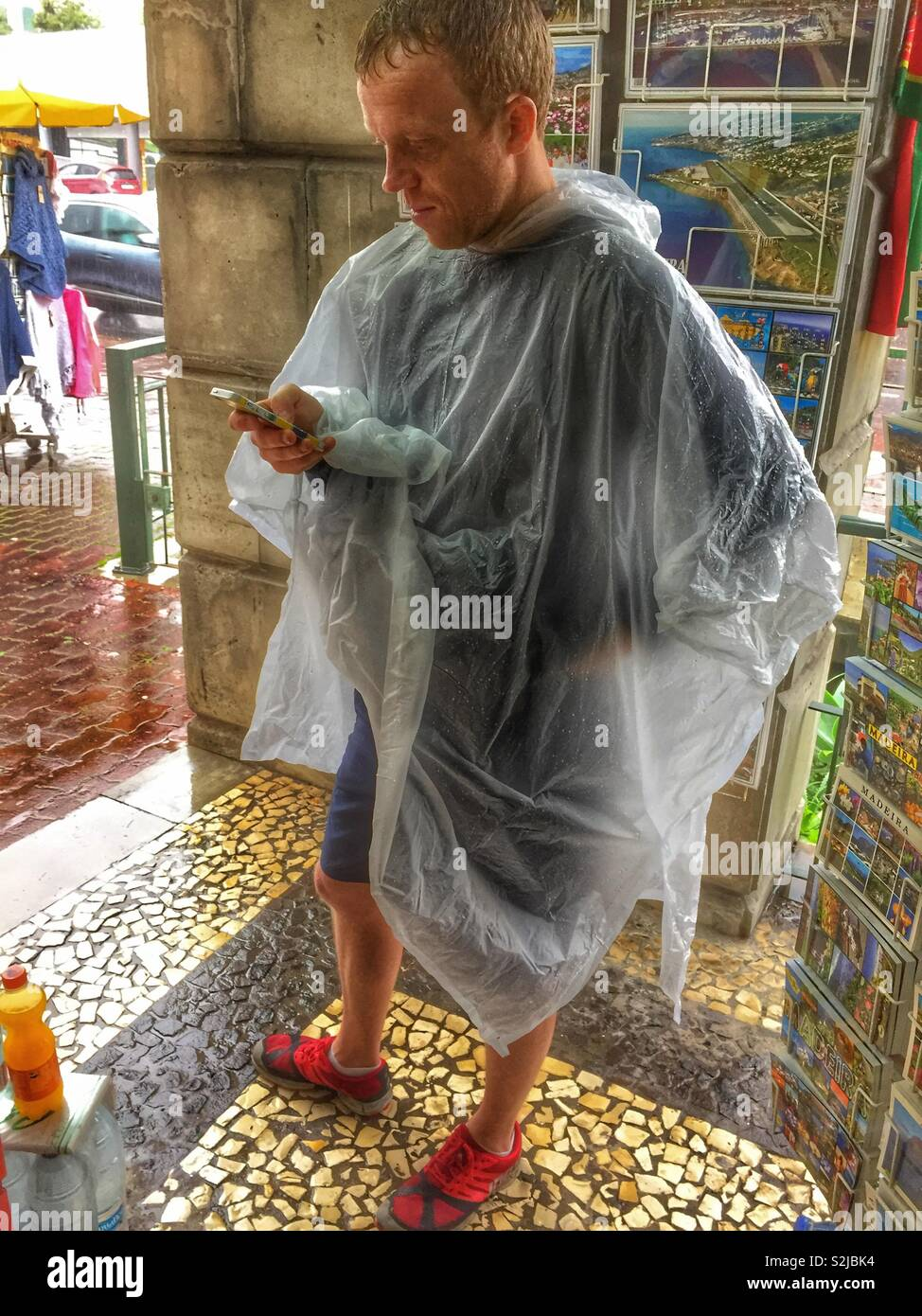 Man using a mobile phone wearing a poncho. - Stock Image