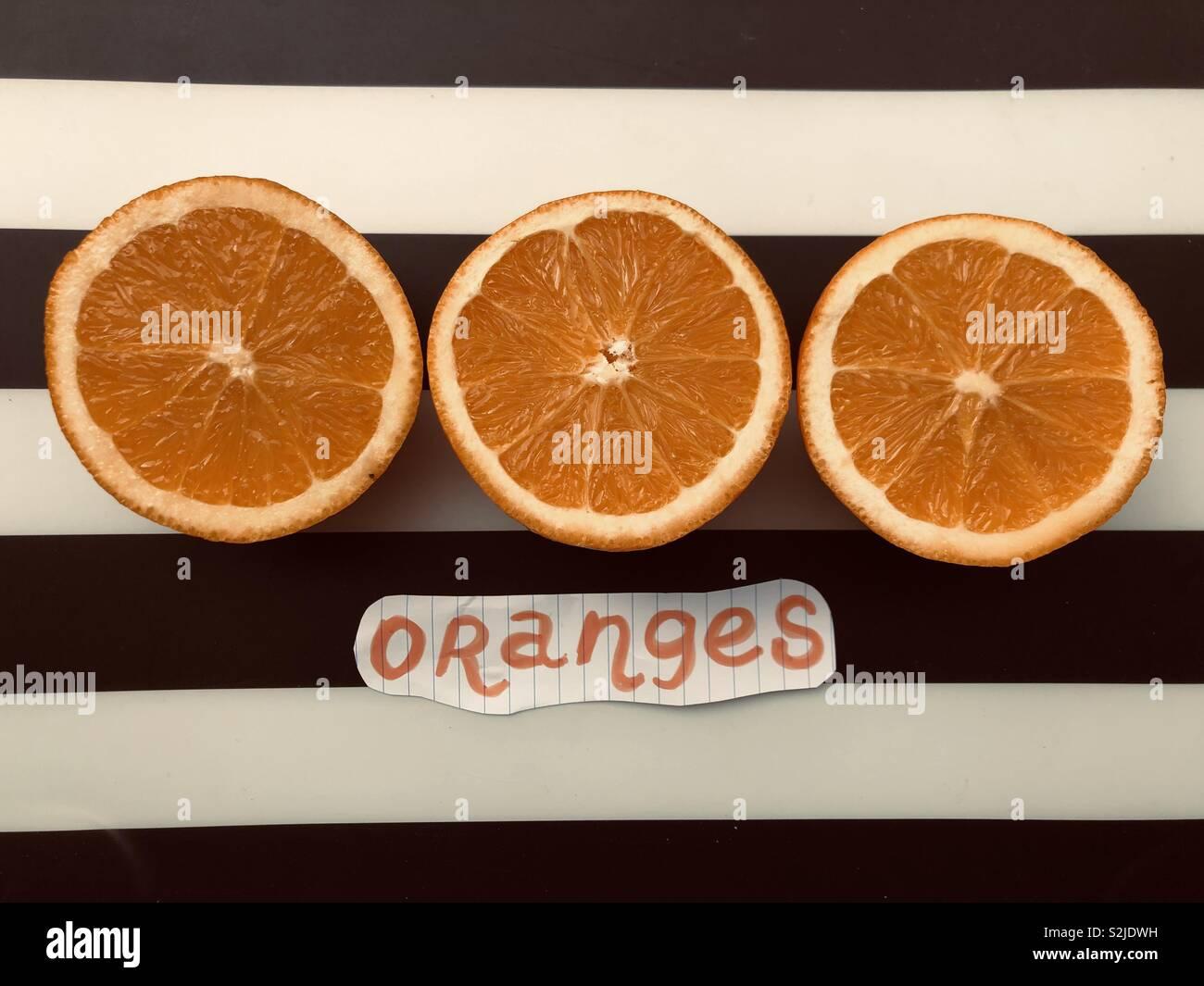 Three oranges against black and white background - Stock Image