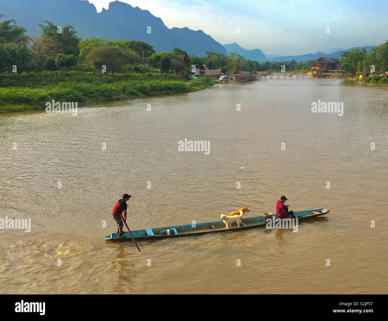 River in Vang Vieng Laos with people ferrying dogs over river Stock Photo