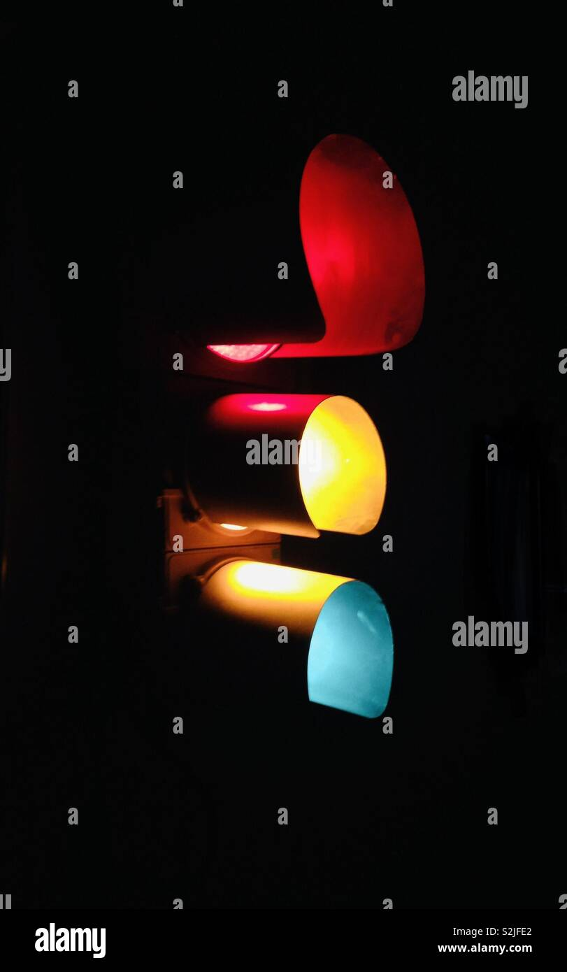 Stoplight glowing in the dark all colors on - Stock Image