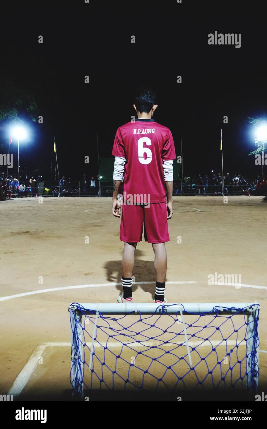 Soccer by night with tiny goal: single player in red jersey waiting for some actuon! - Stock Image