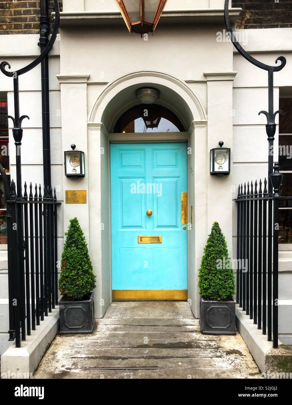 A Quaint Home In London England A Bright Cheery Turquoise Blue Front Door Flanked By Topiary Trees Stock Photo Alamy