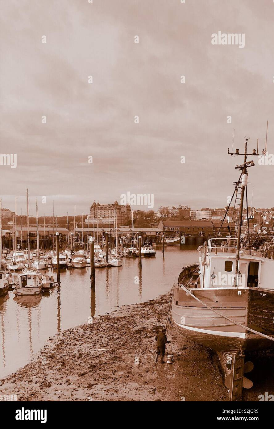 Man painting a boat in a harbour, in sepia tones - Stock Image