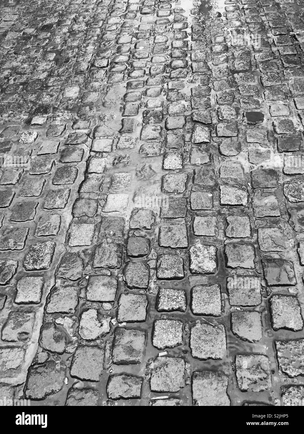 Wet and damp cobblestones on a rainy day.  Rain pouring down on the roads and streets of the ground. Cobbles soaked with rain.  Murky weather - Stock Image