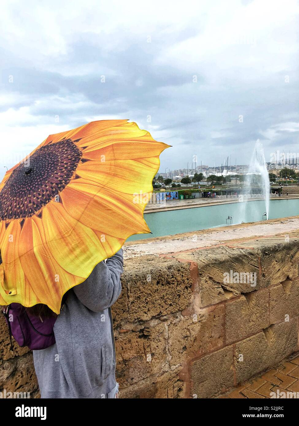 A girl is standing on a rainy day under an yellow umbrella in the form of a sunflower near an ancient stone fence against the background of a pond with a fountain and a sea port - Stock Image